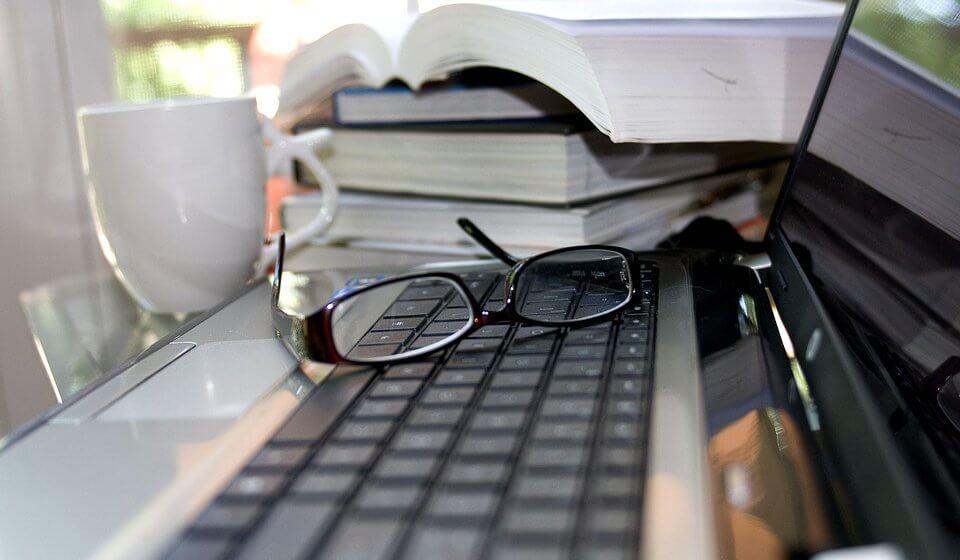 Imagem que mostra alguns livros empilhados ao lado de um notebook e um óculos.