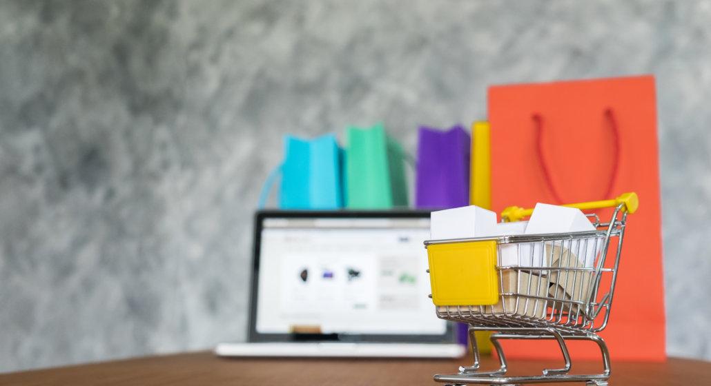 Imagem de um mini carrinho de compras com algumas sacolas e um notebook ao fundo da foto.
