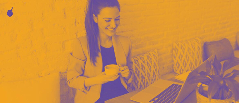 Uma mulher tomando café e lendo o conteúdo do blog em um notebook